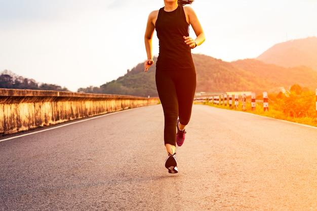 Esporte mulher correndo em uma estrada. fitness mulher treinando ao pôr do sol Foto Premium