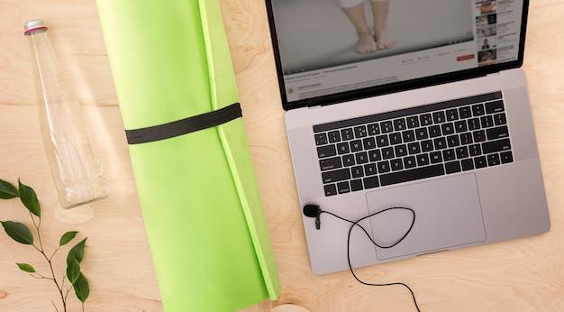 Esporte on-line ou curso de formação conceito vista superior laptop com tapete de ioga e garrafa de vidro de água no chão de madeira Foto Premium