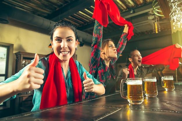 Esporte, pessoas, lazer, amizade, conceito de entretenimento - fãs de futebol feminino felizes ou bons jovens amigos bebendo cerveja, comemorando a vitória em um bar ou pub. conceito de emoções positivas humanas Foto gratuita