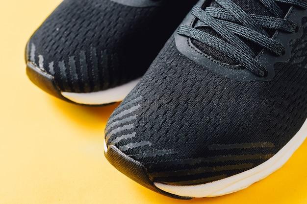 Esportes executando tênis pretos sobre fundo amarelo Foto Premium