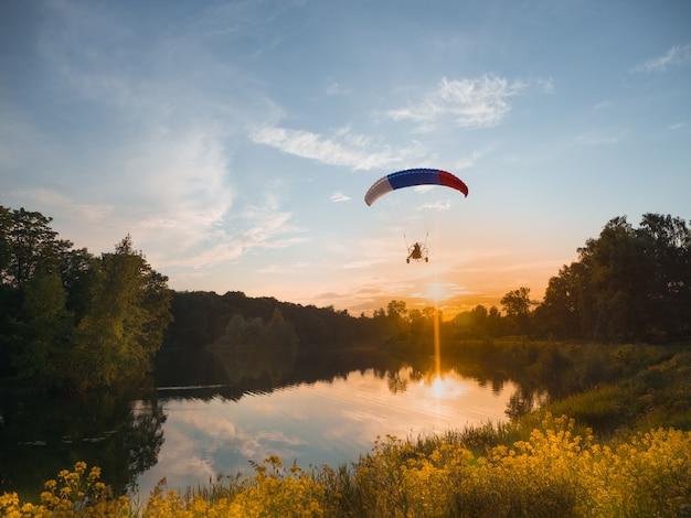 Esportes extremos. pára-quedas motorizado à noite contra o céu azul Foto Premium