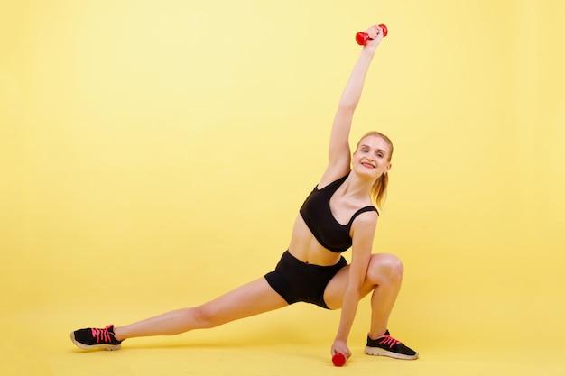 Esportes menina treina com halteres em um espaço amarelo Foto Premium