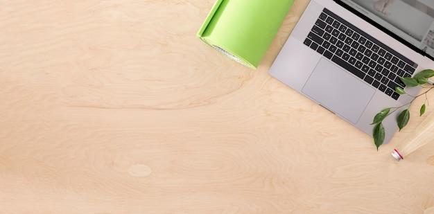 Esportes on-line ou vista superior do conceito de curso de treinamento. laptop com tapete de ioga na vista superior do piso de madeira Foto Premium