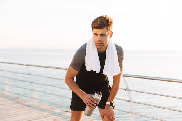 Esportista adulta em agasalho com toalha na água potável do pescoço da caneca de garrafa térmica, depois de treino no cais de madeira à beira-mar na manhã Foto Premium