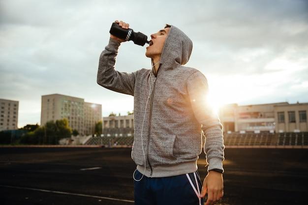 Esportista bebendo água depois de correr, malhar, com fones de ouvido Foto gratuita