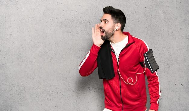 Esportista bonita gritando com a boca aberta para o lado sobre a parede texturizada Foto Premium