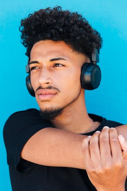 Esportista com fones de ouvido, esticando o braço Foto gratuita