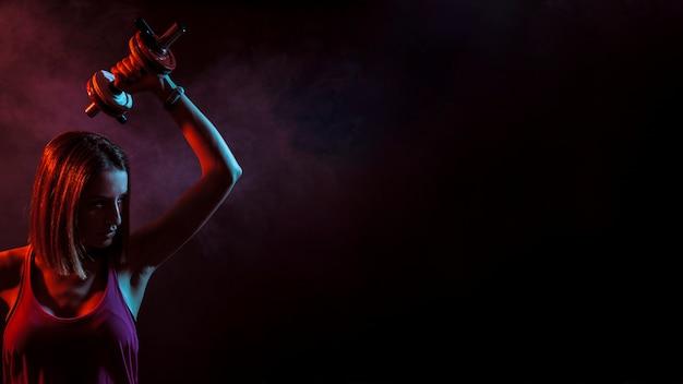 Esportista confiante com dumbbell no escuro Foto gratuita