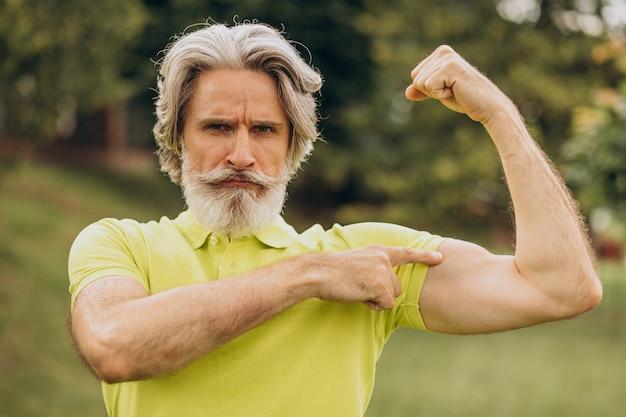 Esportista de meia-idade apontando no bíceps Foto gratuita