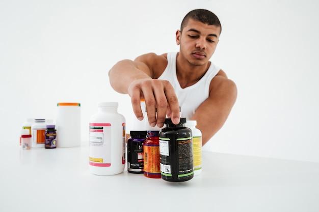 Esportista de pé sobre uma parede branca segurando vitaminas Foto gratuita
