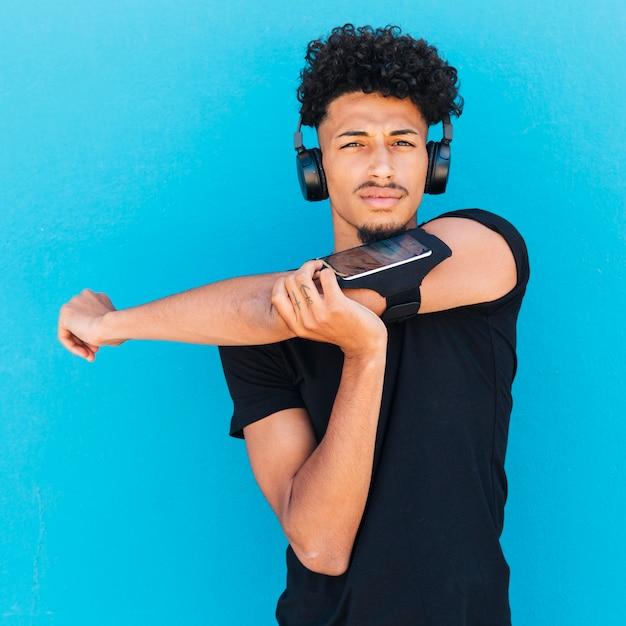Esportista em fones de ouvido e braçadeira de alongamento Foto gratuita