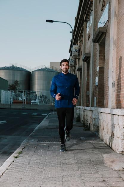 Esportista grave correndo na rua vazia Foto gratuita