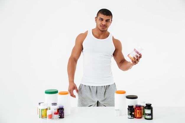 Esportista segurando vitaminas e pílulas de esporte. Foto gratuita