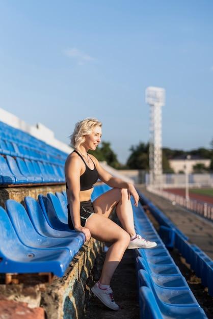 Esportiva feminina no estádio sentado Foto gratuita