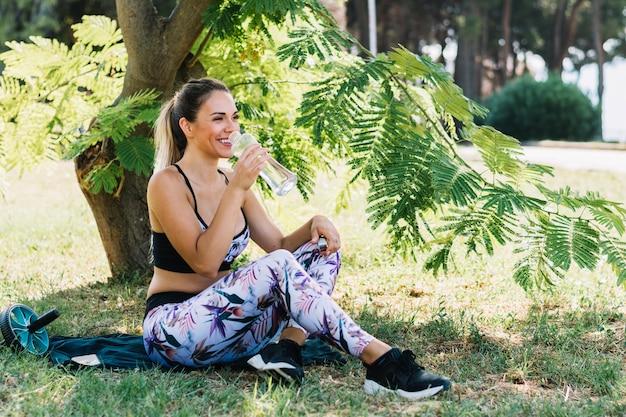 Esportiva jovem desfrutando de água potável da garrafa no jardim Foto gratuita
