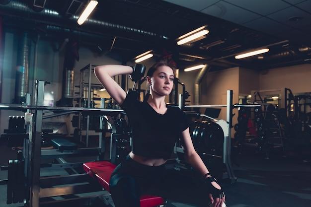 Esportiva jovem fazendo exercício com halteres no centro de fitness Foto gratuita