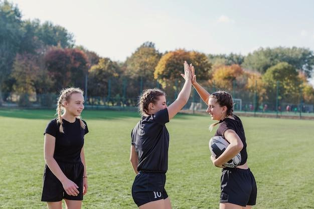 Esportivas meninas segurando uma bola de futebol e mais cinco Foto gratuita
