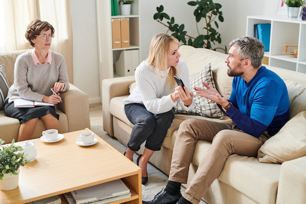 Esposa irritada mostrando sms da amante para o marido na sessão de psicologia Foto Premium