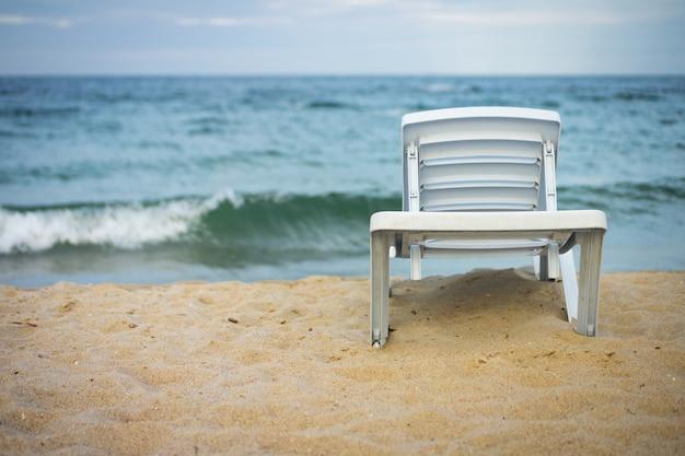 Espreguiçadeira branca de plástico na praia vazia Foto Premium