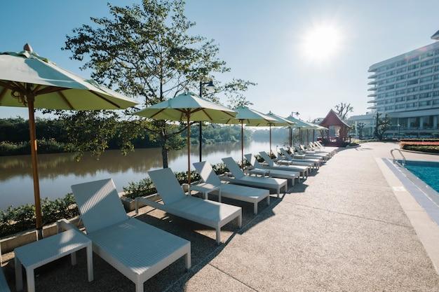 Espreguiçadeira e piscina no hotel Foto gratuita