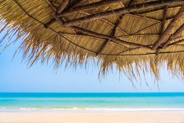 Espreguiçadeira vazia com guarda-chuva no céu azul do mar da praia para viagens de lazer Foto gratuita