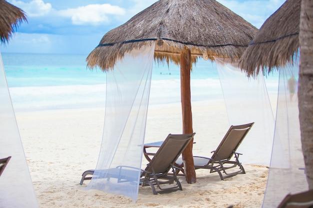 Espreguiçadeiras de praia sob guarda-sóis de palha na plage tropical Foto Premium