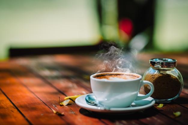Espuma de café quente latte cappuccino espiral na mesa de madeira na loja de café Foto Premium