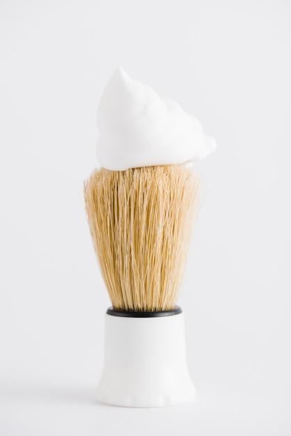 Espuma sobre o pincel de barba sintética contra o pano de fundo branco Foto gratuita