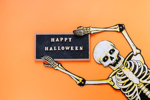 Esqueleto assustador com lousa Foto gratuita