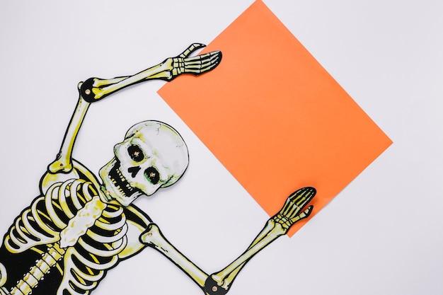 Esqueleto com folha de papel nas mãos Foto gratuita
