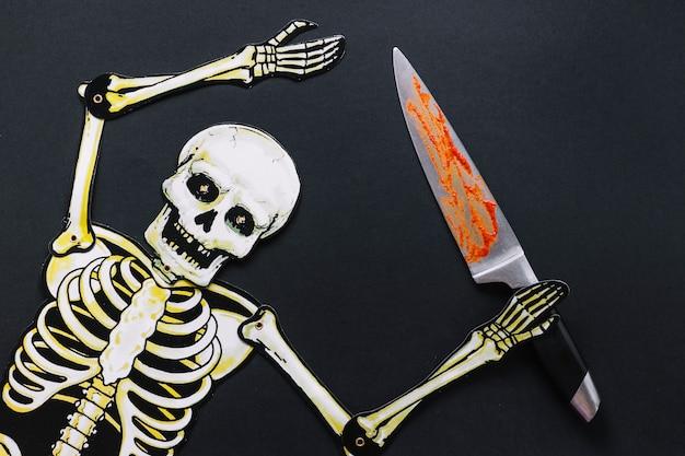 Esqueleto de papel com faca ensanguentada Foto gratuita