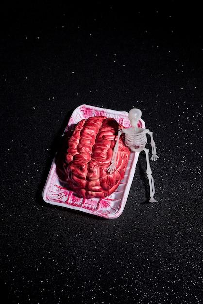 Esqueleto sentado além de uma composição cerebral Foto gratuita