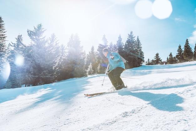 Esquiador de esqui em declive durante o dia ensolarado nas altas montanhas Foto gratuita