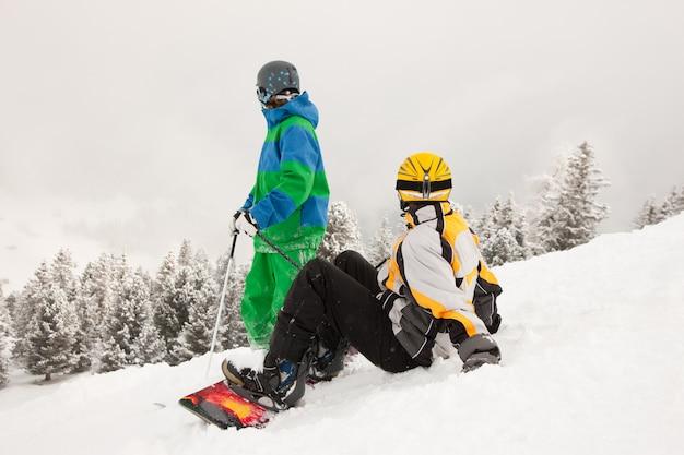 Esquiador e snowboarder na montanha Foto Premium