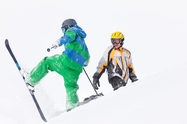 Esquiador e snowboarder na neve Foto Premium