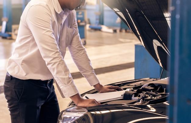 Esta carreira homem saleman inspeção empresarial escrevendo nota no bloco de notas ou livro, papel com fundo desfocado do carro Foto Premium