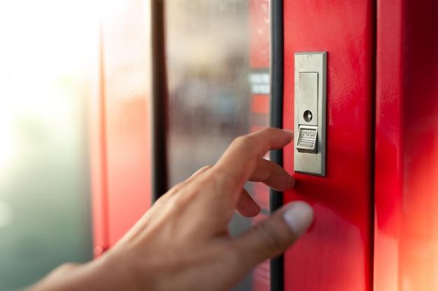 Esta mão será pressione o botão para abrir a porta do extintor de incêndio Foto Premium