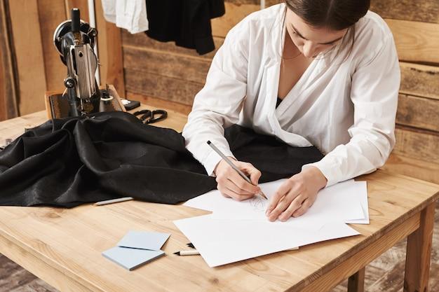 Esta peça de roupa será o meu melhor. tiro de ângulo lateral do esgoto talentoso ocupado criando design de roupa nova, de pé em sua oficina perto da mesa com máquina de costura e tecido. imaginação é a chave Foto gratuita