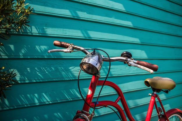 Estacionamento de bicicleta vintage vermelho close-up na parede de madeira azul com espaço de cópia Foto Premium