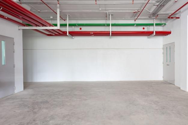 Estacionamento interior da garagem edifício industrial hidrante com mangueiras de água em edifício industrial espaço vazio para o fundo da indústria. Foto Premium