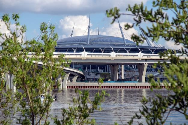 Estádio de futebol no fundo de árvores verdes e um rio Foto Premium