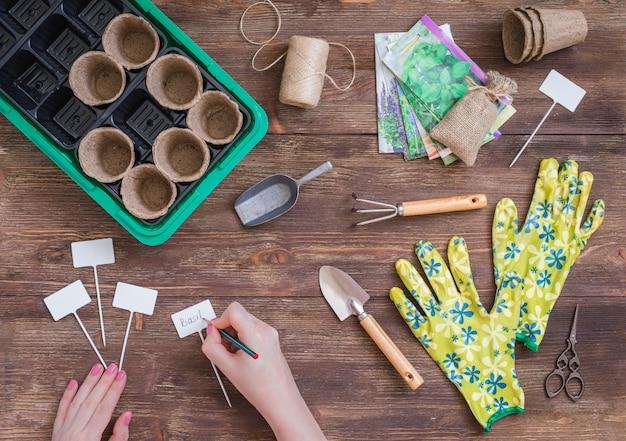 Estágios de plantio de sementes, preparação, mãos de mulher, escrevendo os nomes de plantas, ferramentas de jardineiros e utensílios Foto Premium