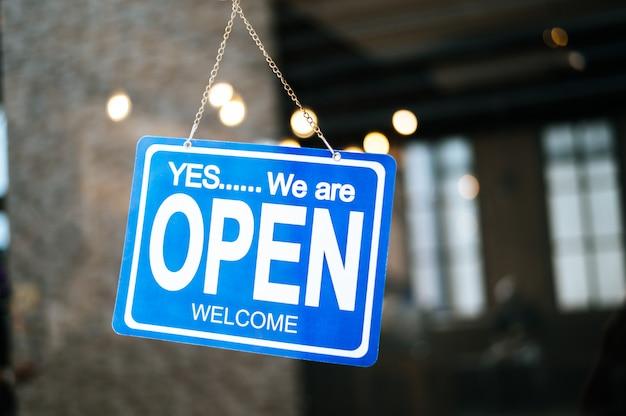Estamos abertos, assine bem através do vidro da janela no restaurante Foto gratuita