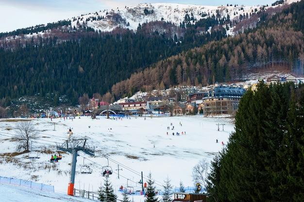Estância de esqui em um belo dia de inverno; esquiadores e praticantes de snowboard esquiando ladeira abaixo até a base de um teleférico; árvores e montanhas Foto Premium