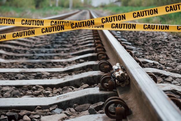 Estar ciente. explosivo perigoso deitado na ferrovia. fita isolante amarela na frente Foto gratuita