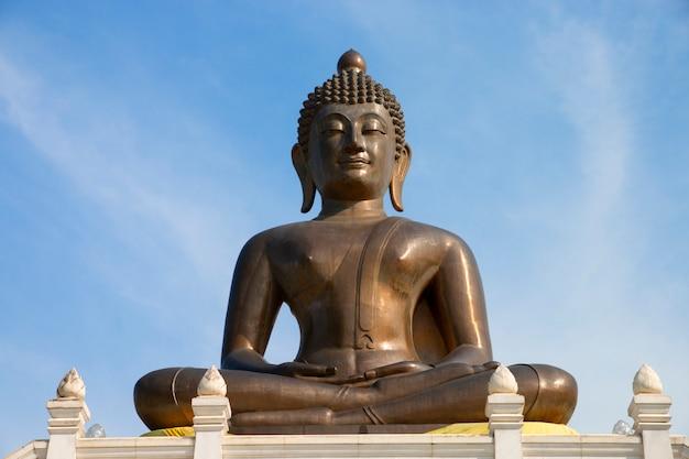 Estátua de buddha no templo com fundo do céu azul. Foto Premium