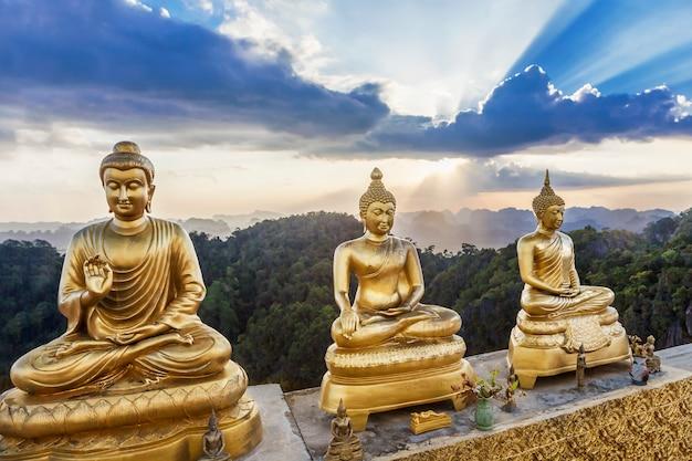 Estátuas de buda com fundo por do sol de beleza Foto Premium