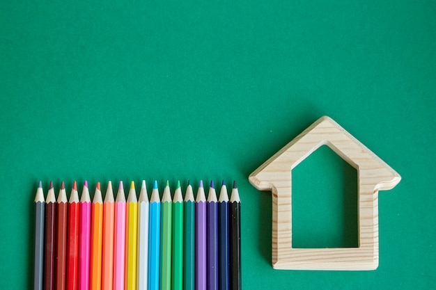 Estatueta de casa de madeira e vários lápis coloridos isolar sobre fundo verde Foto Premium