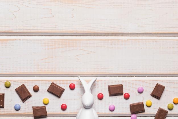 Estatueta de páscoa branca no meio de pedaços de chocolate e doces de gema em fundo de madeira Foto gratuita