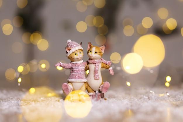 Estatuetas decorativas de um tema de natal. estatueta de giros abraços gatos vestidos com uma camisola de malha, cachecol e chapéu Foto Premium